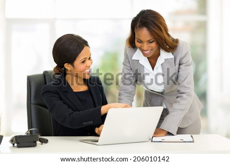 two african business women working at the office on a computer - stock photo