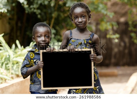 Two African Children Holding Blackboard. Two children posing in the streets of Bamako, Mali. - stock photo