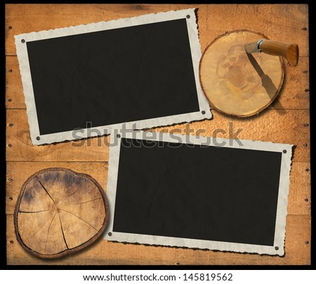 Two aged photo frames on wooden background with sections of the trunk and folding knife - stock photo