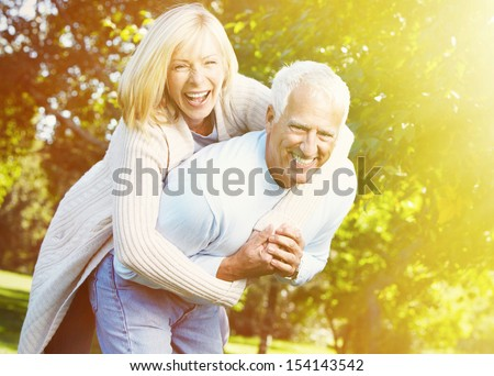 Two aged smiling people over park background - stock photo
