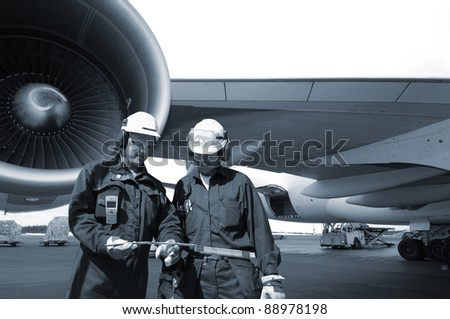 two airplane mechanics with giant jet engine in background, blue toning idea.