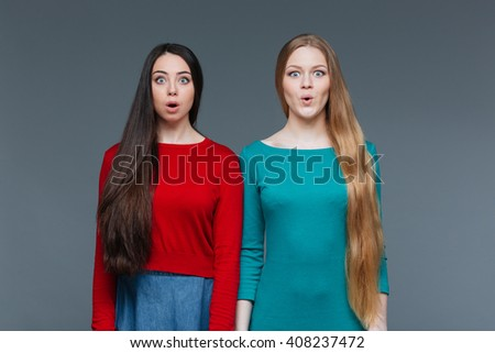 Two amazed girl standing over gray background and looking at camera - stock photo