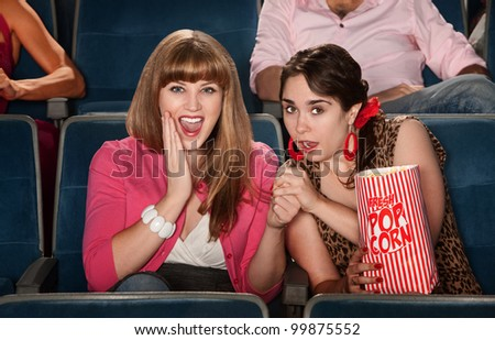 Two amazed ladies with bag of popcorn in theater