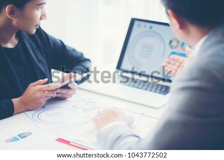 Two analysts discussing online data in front of laptop