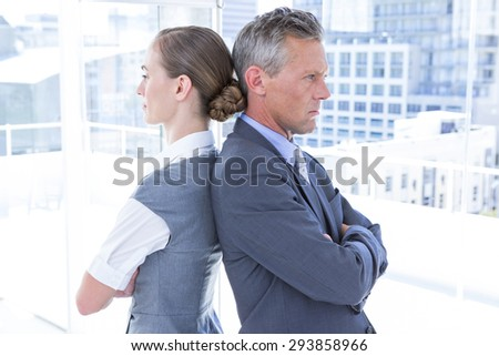 Two angry business colleagues standing back to back in the office - stock photo