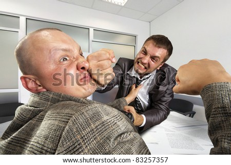 Two angry businessmen fighting in the office - stock photo