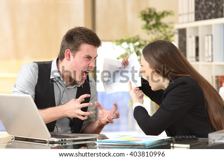 Two angry businesspeople arguing furious showing a negative growth graph at office - stock photo