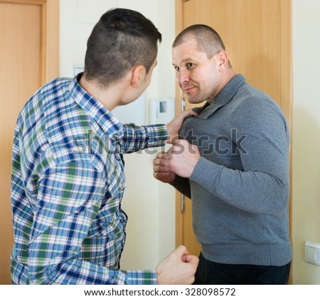 Two angry young males having fight indoor - stock photo