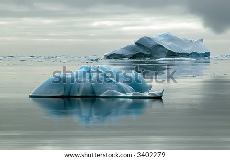 Two Antarctic icebergs in the Southern Ocean on a nearly flat sea. Picture was taken during a 3-month research expedition. - stock photo