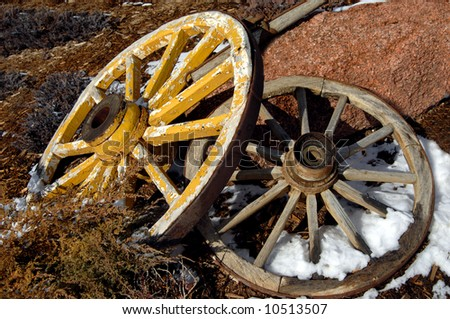 Two antique wagon wheels lay one on top of the other.  Yellow painted one is on top.  Bottom has snow between spokes. - stock photo