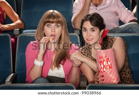 Two anxious women watch movie with bag of popcorn - stock photo