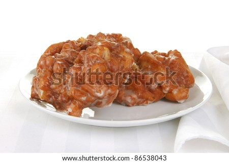 Two apple fritters on a white plate - stock photo