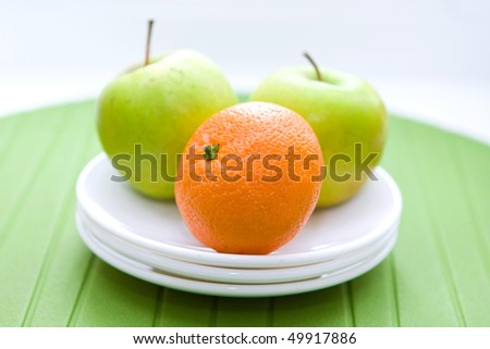 two apples and mandarin on the white plates - stock photo
