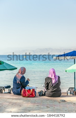 Two arab women lunch at seaside, Aqaba, Jordan, Middle East - stock photo