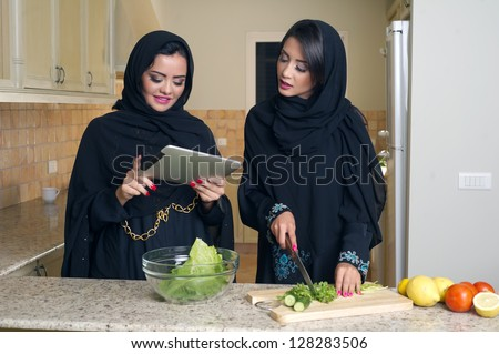 Two Arabian Women gathering cooking & Checking recipe on a Mobile pad - stock photo
