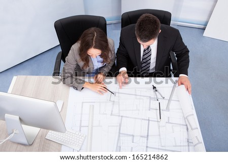 Two Architect Looking At Blue Print Discussing Together - stock photo