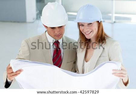 Two architects discussing a construction plan in a building site - stock photo