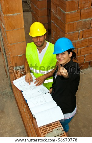 Two architects in a house under construction having a discussion and the woman pointing up to you - stock photo