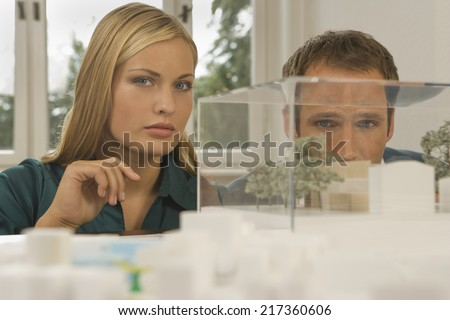 Two architects in front of an architectural model - stock photo
