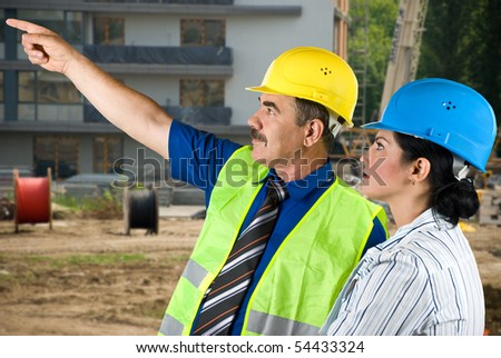 Two architects mature man and young woman working on site,the man pointing to somewhere and they have a discussion