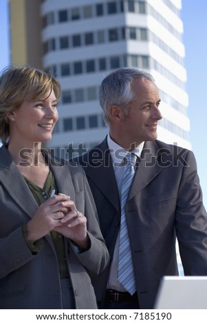 Two architects out on location with a building behind them - stock photo