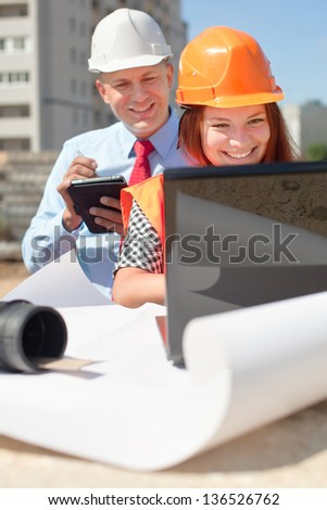 Two architects wearing protective helmet standing in front of building site - stock photo