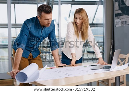 Two architects working on new design at modern office - stock photo