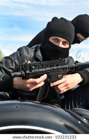 Two armed men riding a motorcycle with a sidecar - stock photo