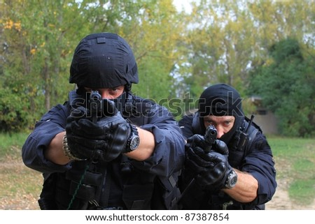 two armed policemen, aiming frontal view details - stock photo