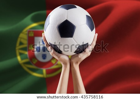 Two arms holding a soccer ball with flag background of Portugal as the participant of european football championship 2016 in France