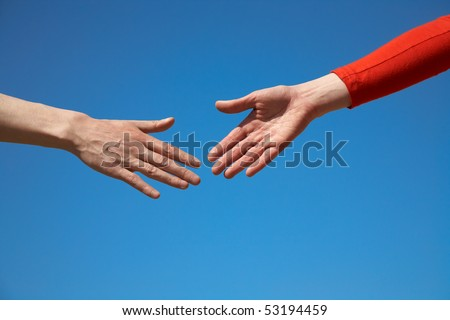 two arms stretching towards each other  to shake against the blue sky - stock photo