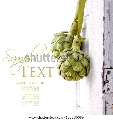 two artichokes hanging from a vintage door, area for copy space - stock photo