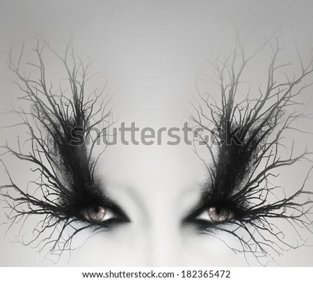 Two artistic female eyes with decoration of  branches around them as a make up in a light grey background - stock photo
