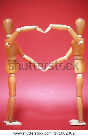 Two artists mannequins using arms to make a heart - stock photo