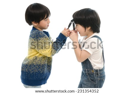 Two asian boy smiling and holding magnifier on a white background - stock photo