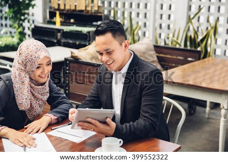 two asian business team meeting at a cafe using tablet pc - stock photo