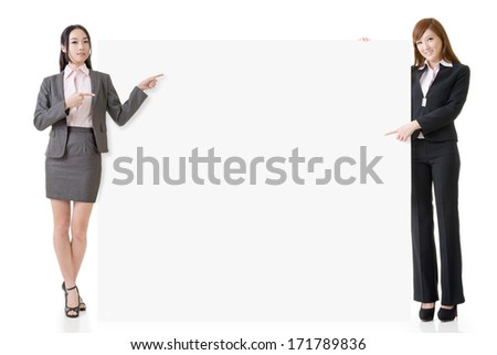 Two Asian business women introduce and hold a blank board, full length portrait isolated on white background. - stock photo
