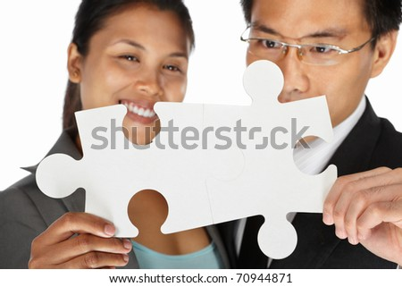 Two Asian businesspeople sucessfuly connect the puzzle pieces - stock photo