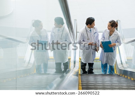 Two Asian doctors on escalator having conversation - stock photo