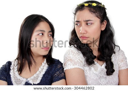Two Asian girl friends having a fight, looking back at each other with suspicious eyes, isolated on white background - stock photo