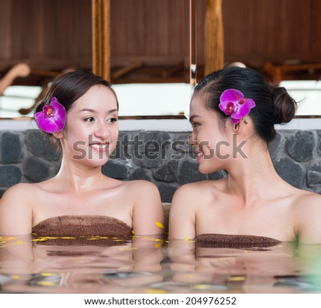 Two Asian girls relaxing in bath in spa salon - stock photo