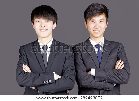 Two asian handsome corporate executives posing confidently on black - stock photo