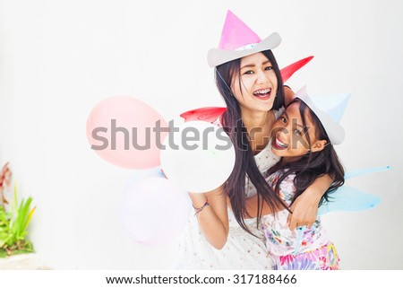 two asian sisters celebrating a holiday wearing party hats and holding balloons (focus on elder sister's eyes) - stock photo