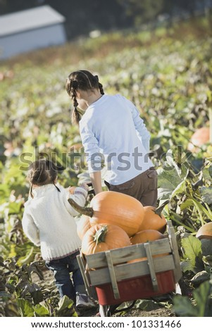 Two Asian sisters pulling wagon through pumpkin patch