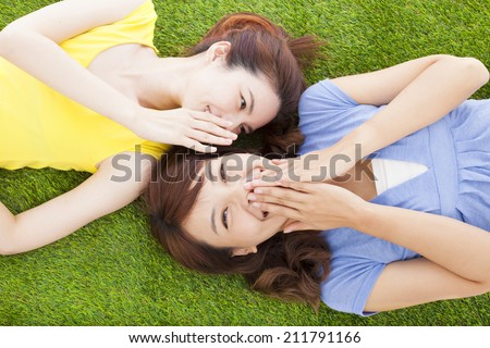 two asian sisters whispering gossip on the grass - stock photo