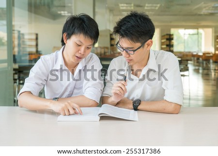 Two Asian students studying together at university - stock photo