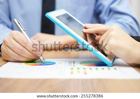 two associates working together on company business data with tablet pc and graph - stock photo