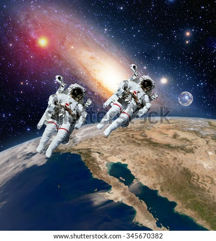 Two astronauts spaceman planet earth outer space moon milky way galaxy. Elements of this image furnished by NASA. - stock photo
