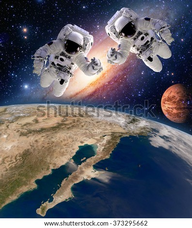 Two astronauts spaceman planet spacewalk outer space walk moon mars galaxy. Elements of this image furnished by NASA. - stock photo