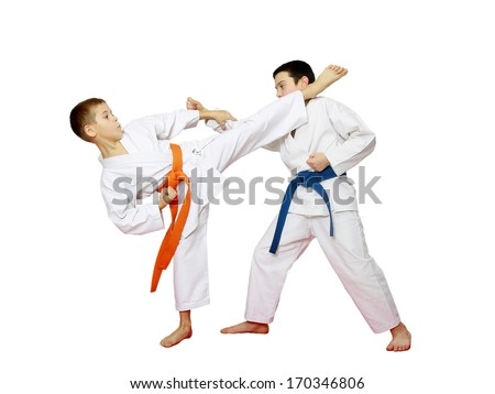 Two athletes with orange and blue belts are doing paired karate exercises